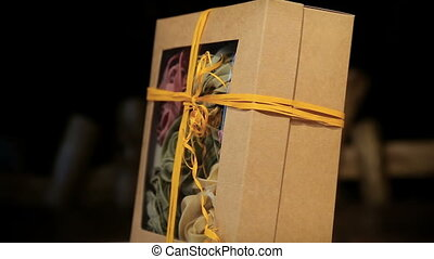 Close-up of various pasta in paper box rotates on black background