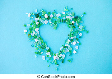 sea glass pieces in the shape of a heart on blue background...