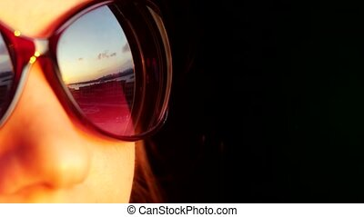 Close up of view beautiful woman's face in sunglasses, standing at window and holding smartphone takes picture on sunset in the city background. That reflected in her sunglasses.