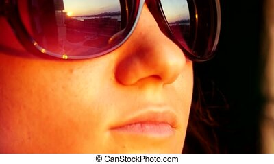 Close up of view pretty woman's face in sunglasses, standing at window and holding smartphone takes picture on sunset in the city background. That reflected in her sunglasses.