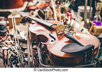 Close up of violin, luthier workshop in background