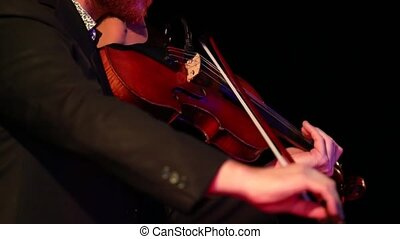 close up of violinist on stage - Close up of a man with ...