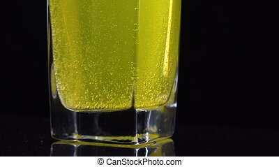 Close up of vitamin C tablet dissolved in a glass of fresh mineral still water on dark backdrop. Macro shot of yellow bubbling liquid with oxygen balls
