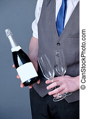 close up of waiter holding bottle of wine and two glasses