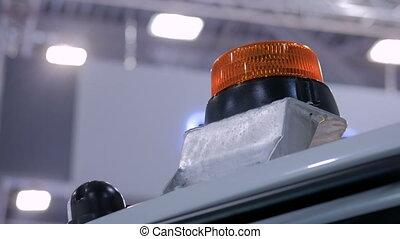 Close up of warning orange beacon flashing on roof of...