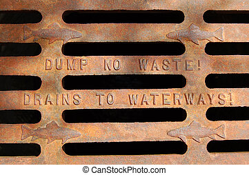 "Close up of water drain ""Dump no waste! Drains to waterways!"""