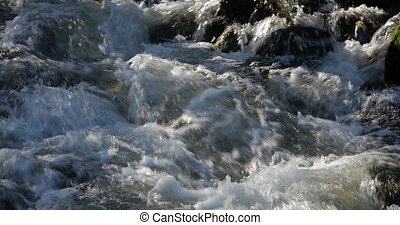 Close up of water stream with white and transparent bubbles.