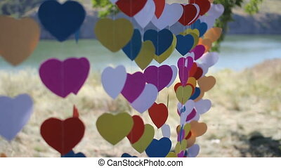 Close up of wedding arch made of hearts on a string sway in the wind