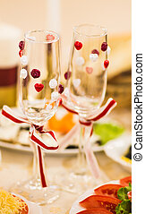 Close-up of wedding decorated champagne glasses on the table