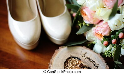 Close up of wedding decoration made of beautiful white shoes, wooden stand for wedding rings and bouquet of flowers.