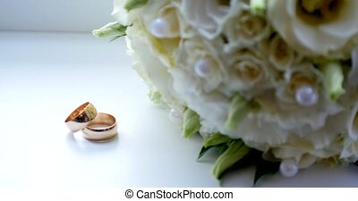 Close up of wedding ring on vintage wooden table with white rose