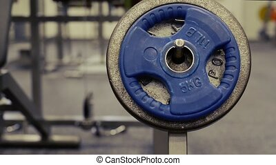 Close up of weights in modern gym. Bench with barbell.