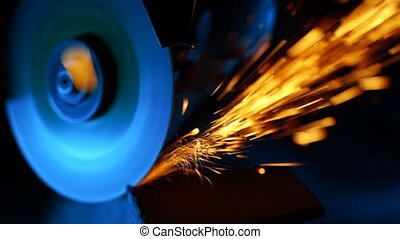 Close-up of welder grinding smooths steel and iron using modern equipment. Industrial production, locksmith industry concept. Sparks from grinding wheel.