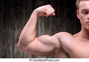 Close up of well formed man demonstrating biceps