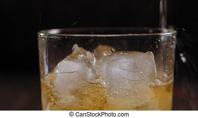 Close-up of whiskey poured into a glass with ice on a brown wooden background