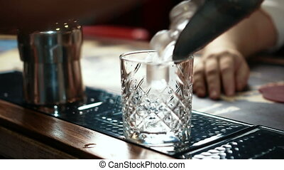 Close up of whisky glass being fulfilled with ice in stylish bar, slow motion.
