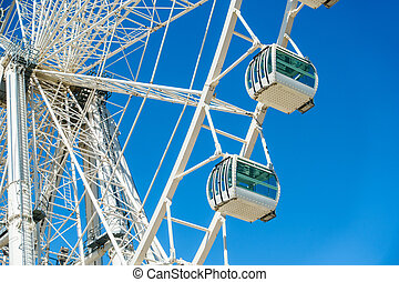 Close-up of white ferris wheel against of clear blue sky