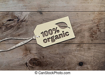 white hang tag cardboard lable with string attached an text 100 percent organic on rustic wooden table
