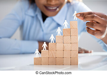 White Human Figures Leading On Top Of Wooden Blocks