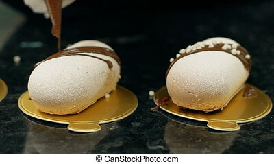 Close up of white pastries on golden plates being decorated...