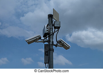 Close up of white security camera and white sky
