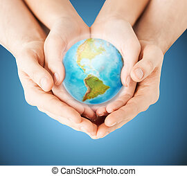 close up of woman and man hands with earth globe
