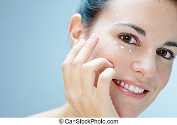 eye cream - close up of woman applying eye cream