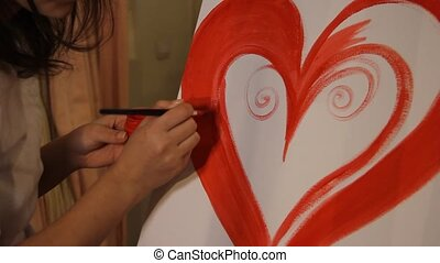 painting a big red heart - close up of woman artist painting...