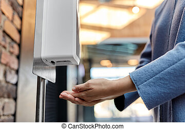 close up of woman at dispenser with hand sanitizer - hygiene...
