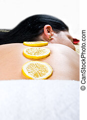 Close up of woman back skin with lemon