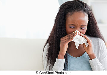 Close up of woman blowing her nose on couch - Close up of ...