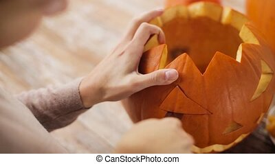 close up of woman carving halloween pumpkin