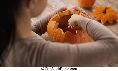 close up of woman carving halloween pumpkin - halloween,...