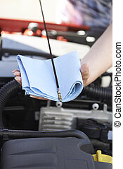 Close-Up Of Woman Checking Car Engine Oil Level On Dipstick