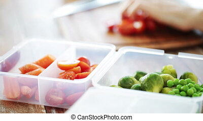 healthy eating, culinary, food, dieting and people concept - close up of woman chopping vegetables and storing them in container at home kitchen