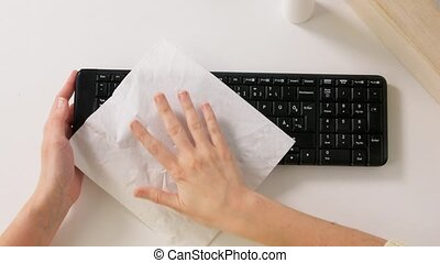 close up of woman cleaning keyboard with sanitizer - hygiene...