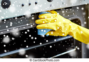 close up of woman cleaning oven at home kitchen