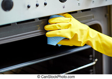 close up of woman cleaning oven at home kitchen - people,...