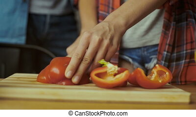 Close up of woman cutting pepper.
