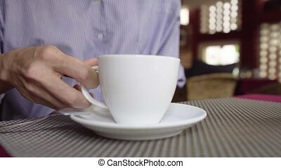 Close-up of woman drinking coffee in cafe.