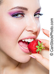 Close up of woman eating strawberry