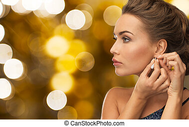 close up of woman fastening diamond earring