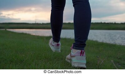 Close-up of woman foot in sneakers are Stepping over grass in sunset