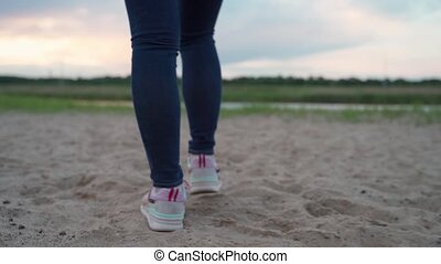 Close-up of woman foot in sneakers are Stepping over sand in sunset