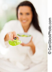 woman giving fresh green salad