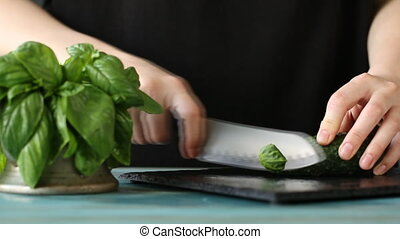 Close-up of woman hand cutting cucumber on black stone