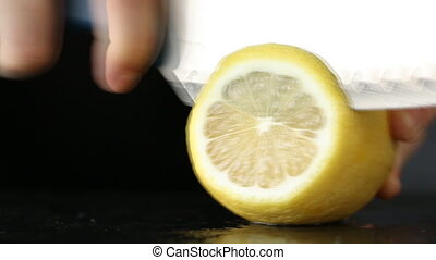 Close-up of woman hand cutting lemon on black stone