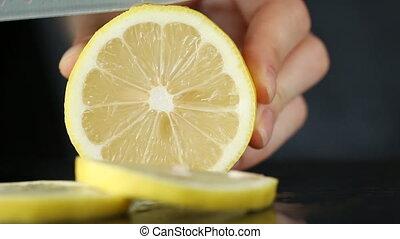 Close-up of woman hand cutting lemon on black stone