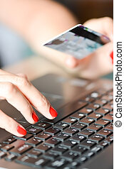 Close-up of Woman hand holding a blue credit card using an laptop for online shopping