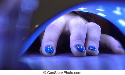 Close up of woman hand in UV led lamp drying gel, nails...